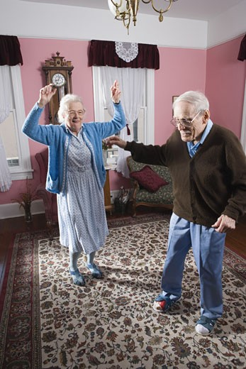 Stock Photo: 1785R-3975 Senior couple dancing in living room