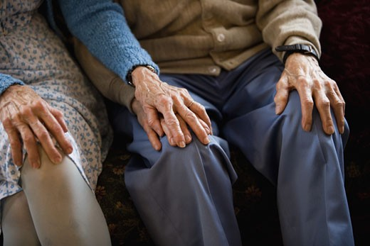 Close-up of senior couple holding hands while sitting : Stock Photo
