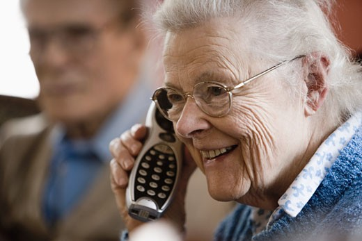 Senior woman talking on cordless phone with senior man in background : Stock Photo