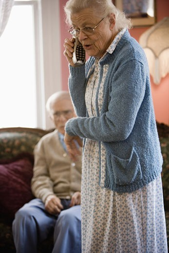 Worried senior woman talking on cordless phone while senior man watches : Stock Photo