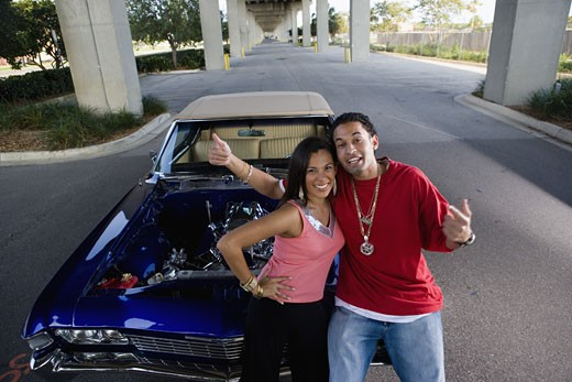 Stock Photo: 1785R-4068 Portrait of a young hip-hop couple standing beside a pimped-up vintage car