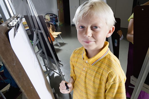 Stock Photo: 1785R-4238 Portrait of a boy standing by a drawing easel in art class
