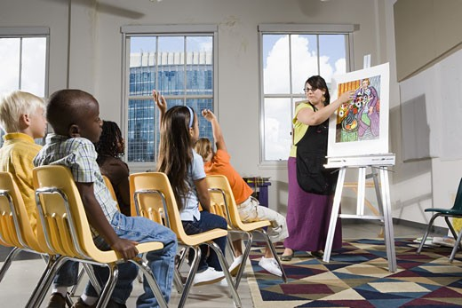 Stock Photo: 1785R-4276 An art teacher standing by easel teaching her young students in art class