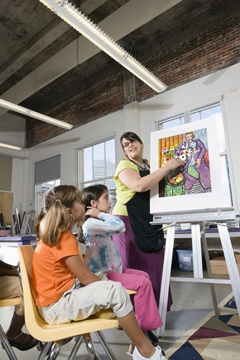 An art teacher standing by easel teaching her young students in art class : Stock Photo