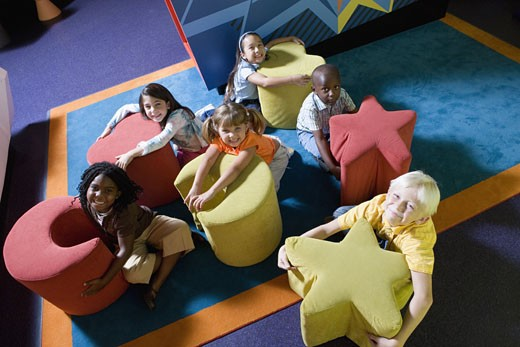 Elevated view of children hugging colorful seats of various shapes : Stock Photo