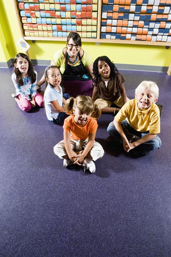 Stock Photo: 1785R-4370 Teacher sitting with young children