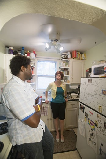 Inter-racial couple talking in kitchen : Stock Photo