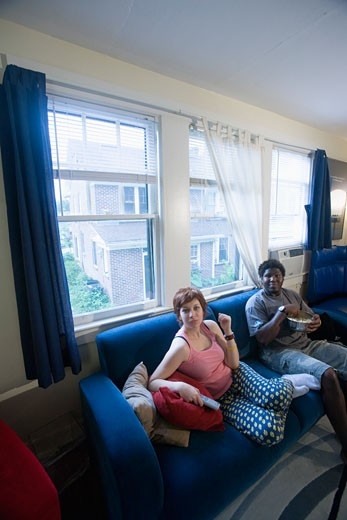 Stock Photo: 1785R-4580 Young inter-racial couple sitting on sofa eating popcorn