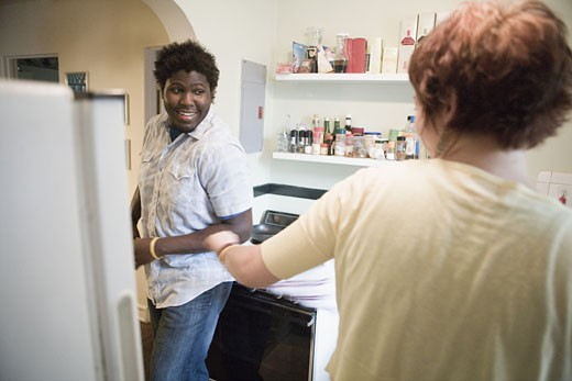 Stock Photo: 1785R-4610 Young inter-racial couple conversing in a kitchen