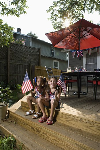 Two little girls in backyard celebrating the 4th of July : Stock Photo