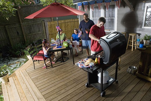 Two families on backyard patio celebrating 4th of July : Stock Photo