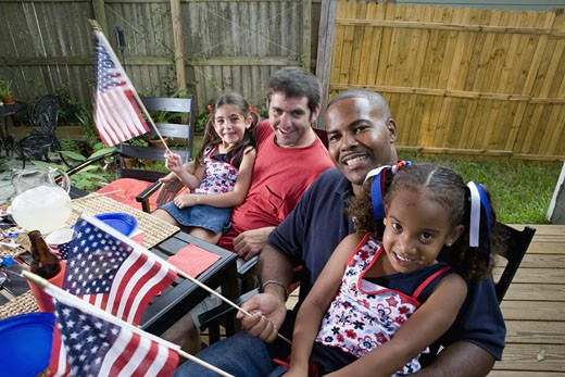 Two young girls with dads at 4th of July cookout waving American flags : Stock Photo