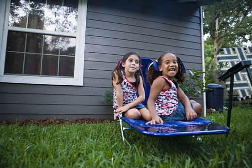 Stock Photo: 1785R-4740 Two girls (6-7) sitting on lawn chair in backyard