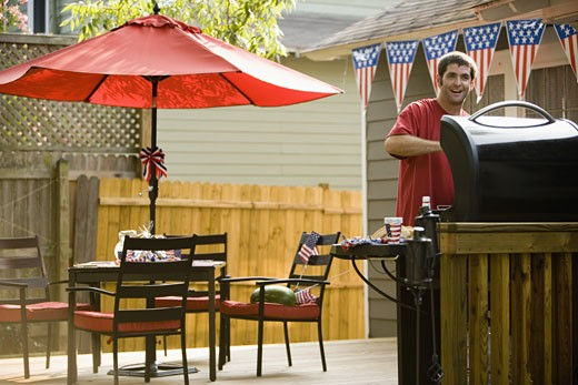 Man cooking on outdoor grill on backyard patio on 4th of July : Stock Photo