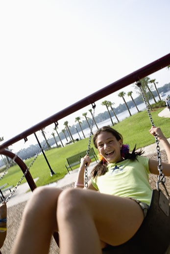 Stock Photo: 1785R-4873 Girl swinging very high and laughing at a playground