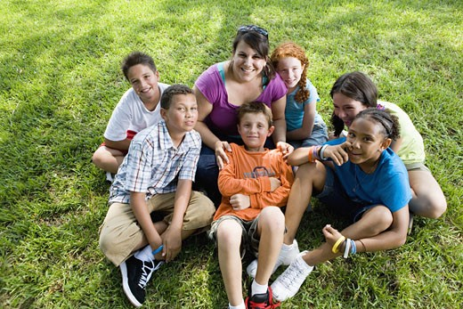Stock Photo: 1785R-4909 Children with their teacher sitting on the grass at a park