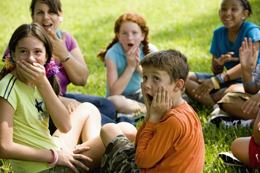Children and their teacher making surprised faces while sitting on the grass at a park : Stock Photo