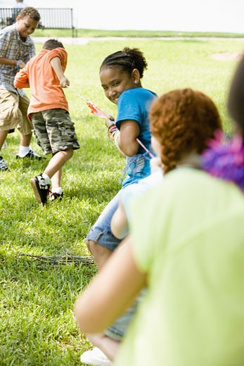 Three boys challenging three girls at tug-of-war at a park : Stock Photo