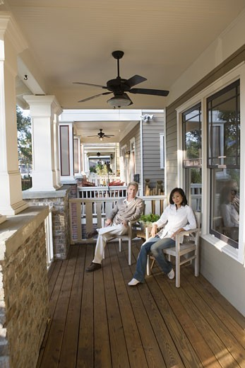 Portrait of an inter-racial couple sitting on the front porch : Stock Photo