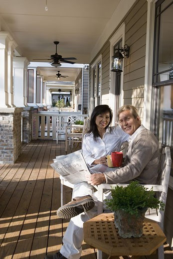 Interracial couple sitting on the front porch : Stock Photo