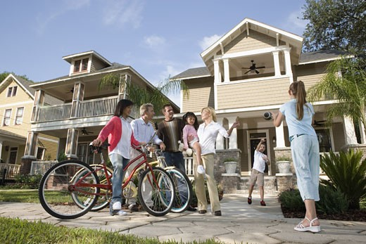 Family with young children conversing with neighbors in front of house : Stock Photo