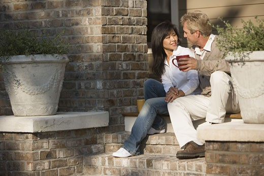 Stock Photo: 1785R-5184 Mature inter-racial couple holding coffee mugs sitting on front steps of their house