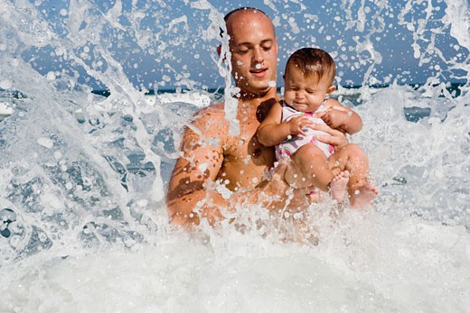 Father playing with baby girl in the ocean waves : Stock Photo