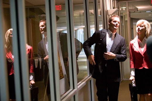 Business people walking and conversing in an office hallway : Stock Photo
