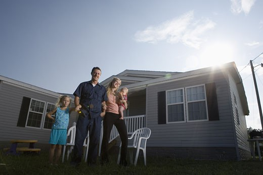 Portrait of a blue-collar family standing in front of a trailer home : Stock Photo