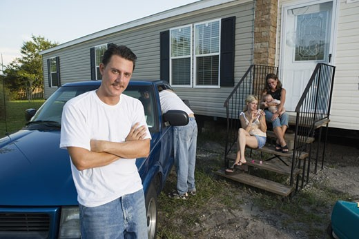 Blue-collar families relaxing in front of a trailer home : Stock Photo