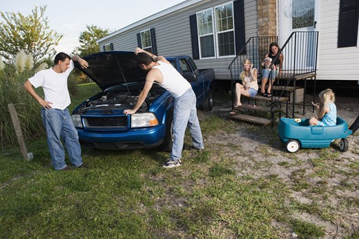 Stock Photo: 1785R-5734 Two men looking under the hood of a pickup truck in front of trailer home