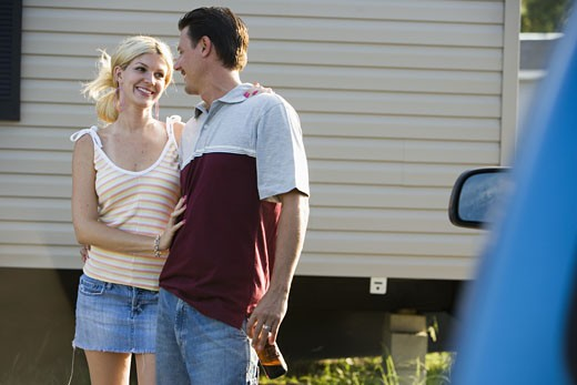 A couple standing by a old van, in front of trailer home : Stock Photo
