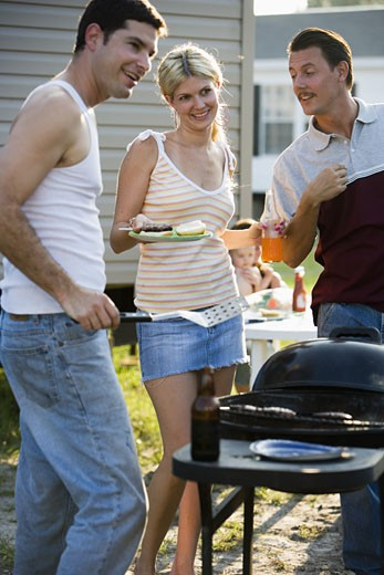Two men and a woman enjoying a cookout in front of a trailer home : Stock Photo