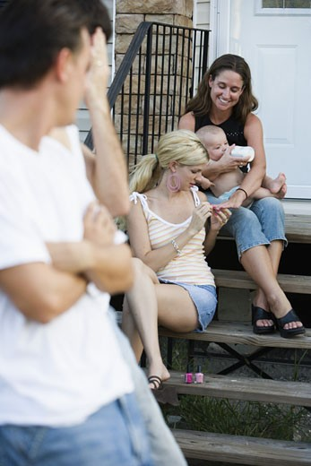 Stock Photo: 1785R-5799 Family and friends relaxing on front steps of a home