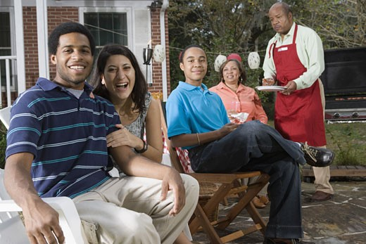 Interracial couple and family enjoying backyard barbeque : Stock Photo