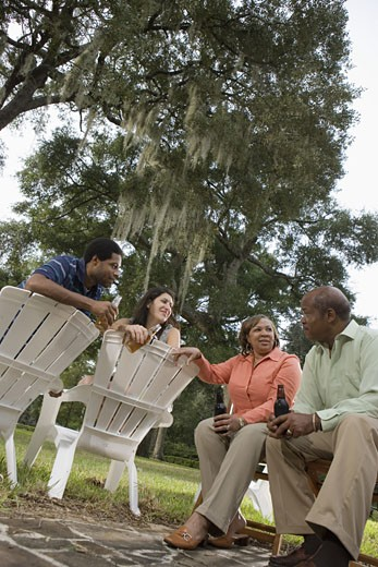 Mature couple having drinks with inter-racial couple while sitting on lawn chairs : Stock Photo