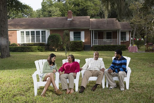 Stock Photo: 1785R-6227 Son and his girlfriend relaxing with his parents backyard
