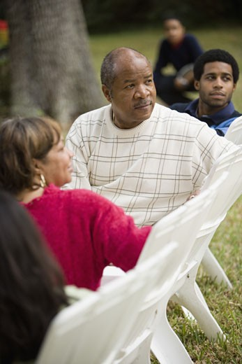 A family sitting on lawn chairs looking behind them : Stock Photo