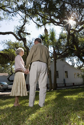 Stock Photo: 1785R-6384 Rear view of mature couple holding hands under oak trees