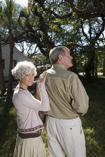 Stock Photo: 1785R-6387 Mature couple standing together under oak trees