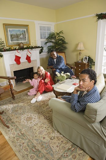 Family in pajamas sitting by fireplace decorated for Christmas : Stock Photo