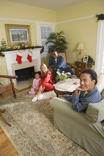 Family in pajamas sitting in living room decorated for Christmas : Stock Photo