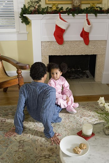 View of brother and sister sitting by fireplace decorated for Christmas, waiting for Santa : Stock Photo