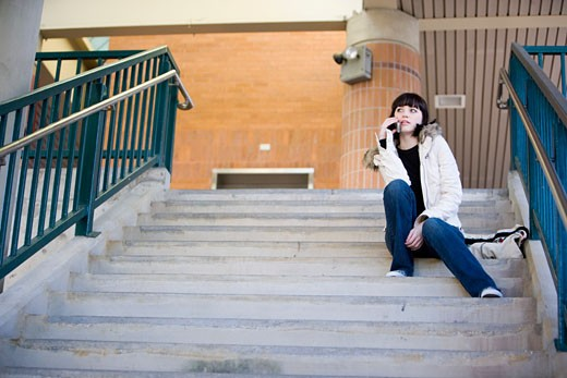 Stock Photo: 1785R-6973 Portrait of a young woman sitting at the top of a concrete staircase on cellphone