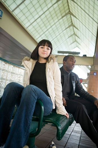 Young inter-racial couple sitting on a bench at a public train station : Stock Photo