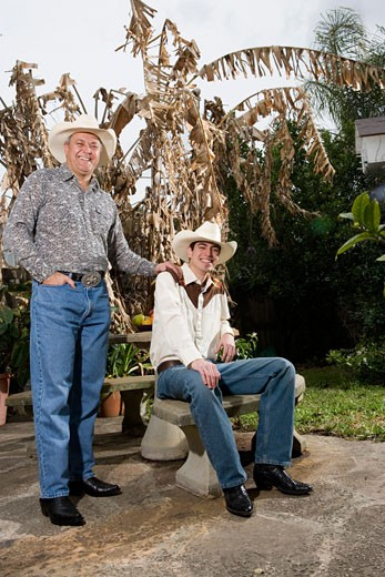 Stock Photo: 1785R-7099 Portrait of Tex-Mex father and son in the backyard of their house