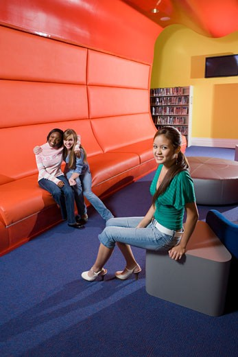 Stock Photo: 1785R-7210 Portrait of teenage girlfriends sitting in the library