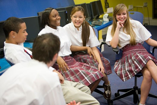 Group of high school students in uniforms conversing : Stock Photo