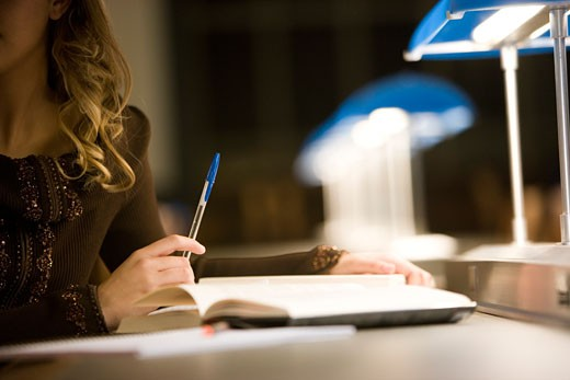 Stock Photo: 1785R-7502 Close-up of a young woman's hands holding a pen and a book in the reading room of a library