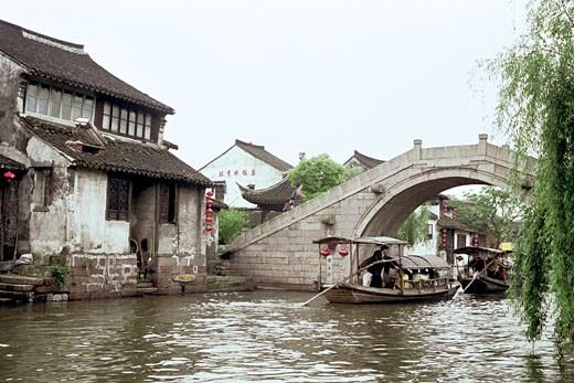Boats passing in lake under bridge, Xitang Town, Jiashan County, Jiaxing City, Zhejiang Province, People's Republic of China, : Stock Photo